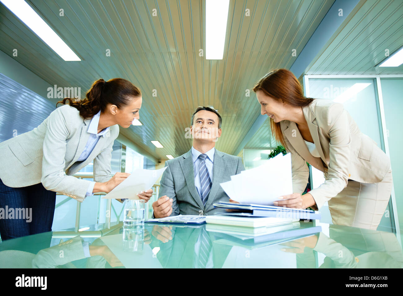 Inspirated boss sitting at workplace surrounded by two secretaries - Stock Image