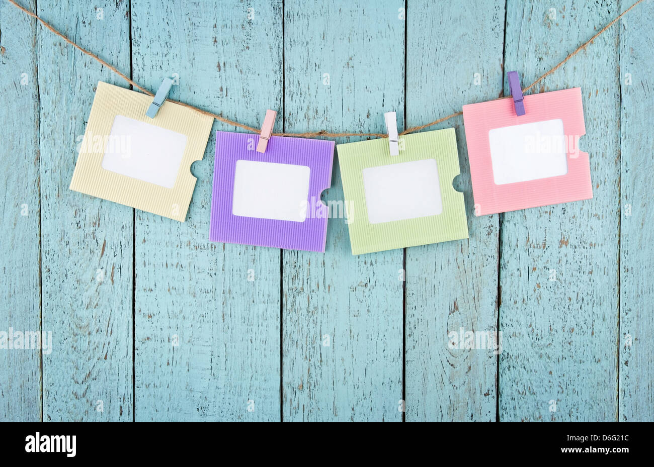 Four empty colorful photo frames or notes paper hanging with clothespins on wooden blue vintage shabby chic background - Stock Image