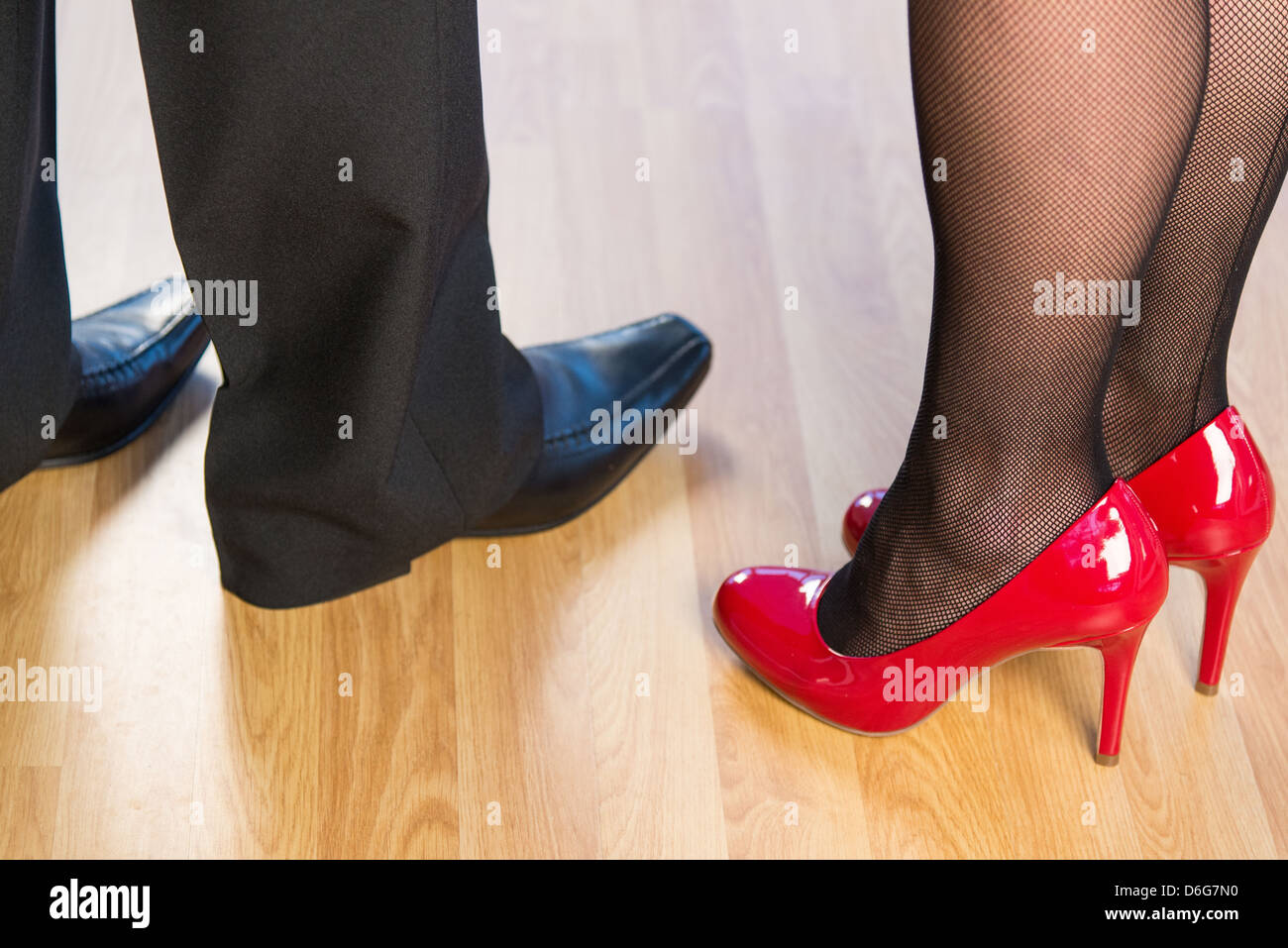 Close up of a young woman and a mans legs with shiny shoes standing on a wooden floor - Stock Image
