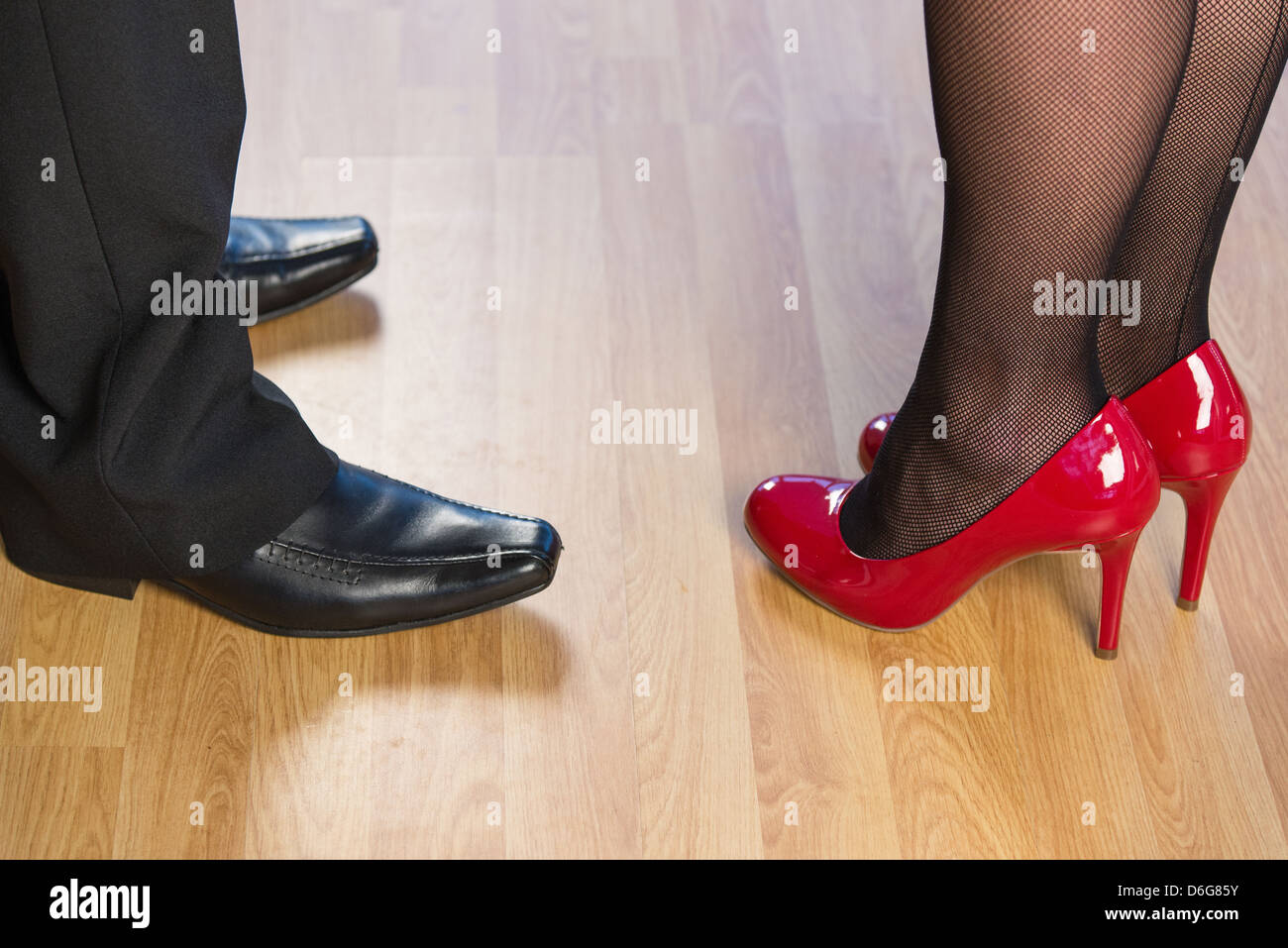 984e7d8c0 Close up of a young women and a mans legs with shiny shoes standing on a