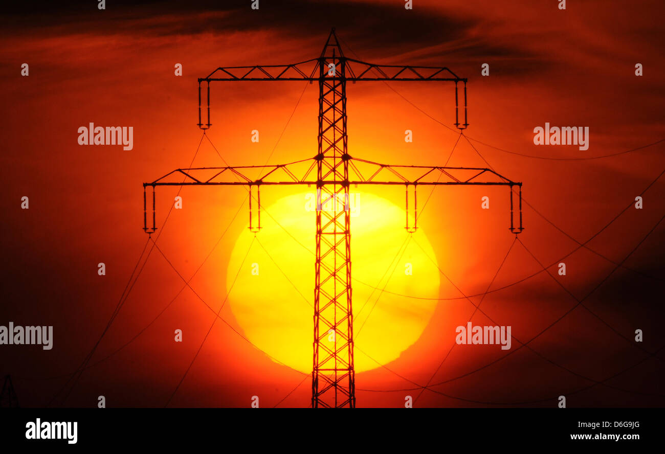 The sun sets behind a pylon near Laatzen, Germany, 06 February 2012. Germany hardly has to deal with power failures - Stock Image
