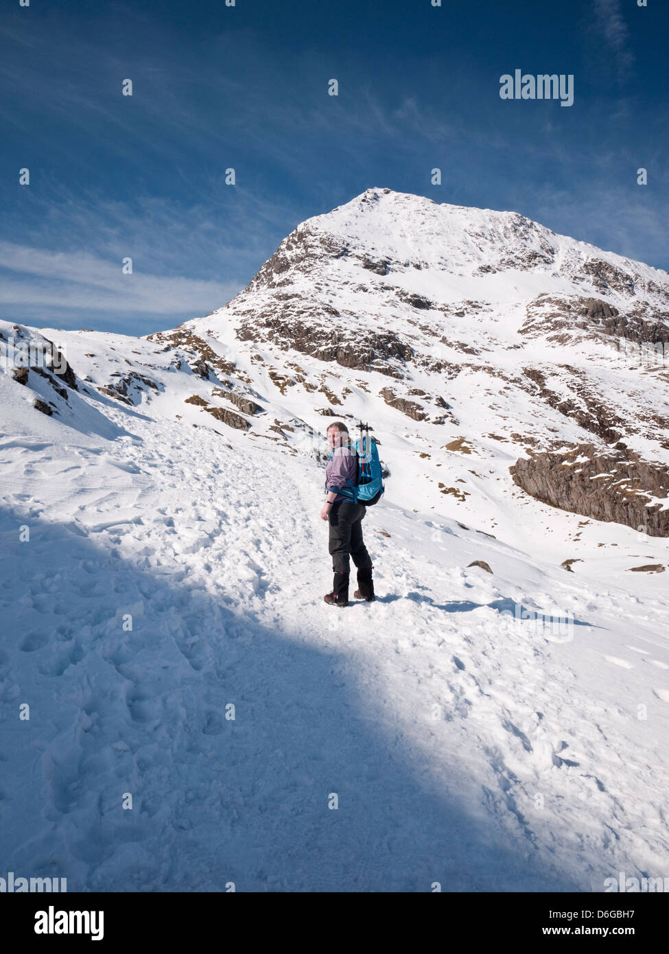 Snowdon in winter conditions - a female hill walker ascends the Pyg track beneath the peak of Crib Goch Stock Photo