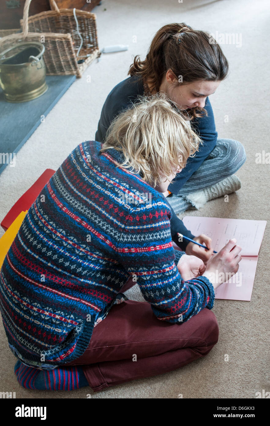 Teenage boy and girl sitting on a living room carpet helping each other with a maths GCSE practice paper and revising - Stock Image