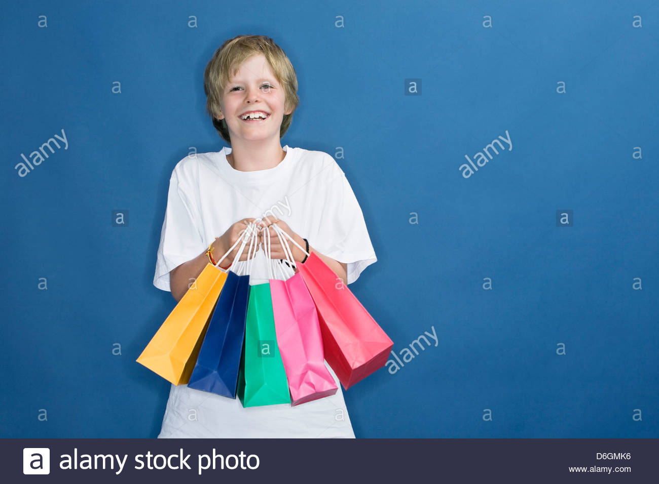 Boy (9) holding paper shopping bags - Stock Image
