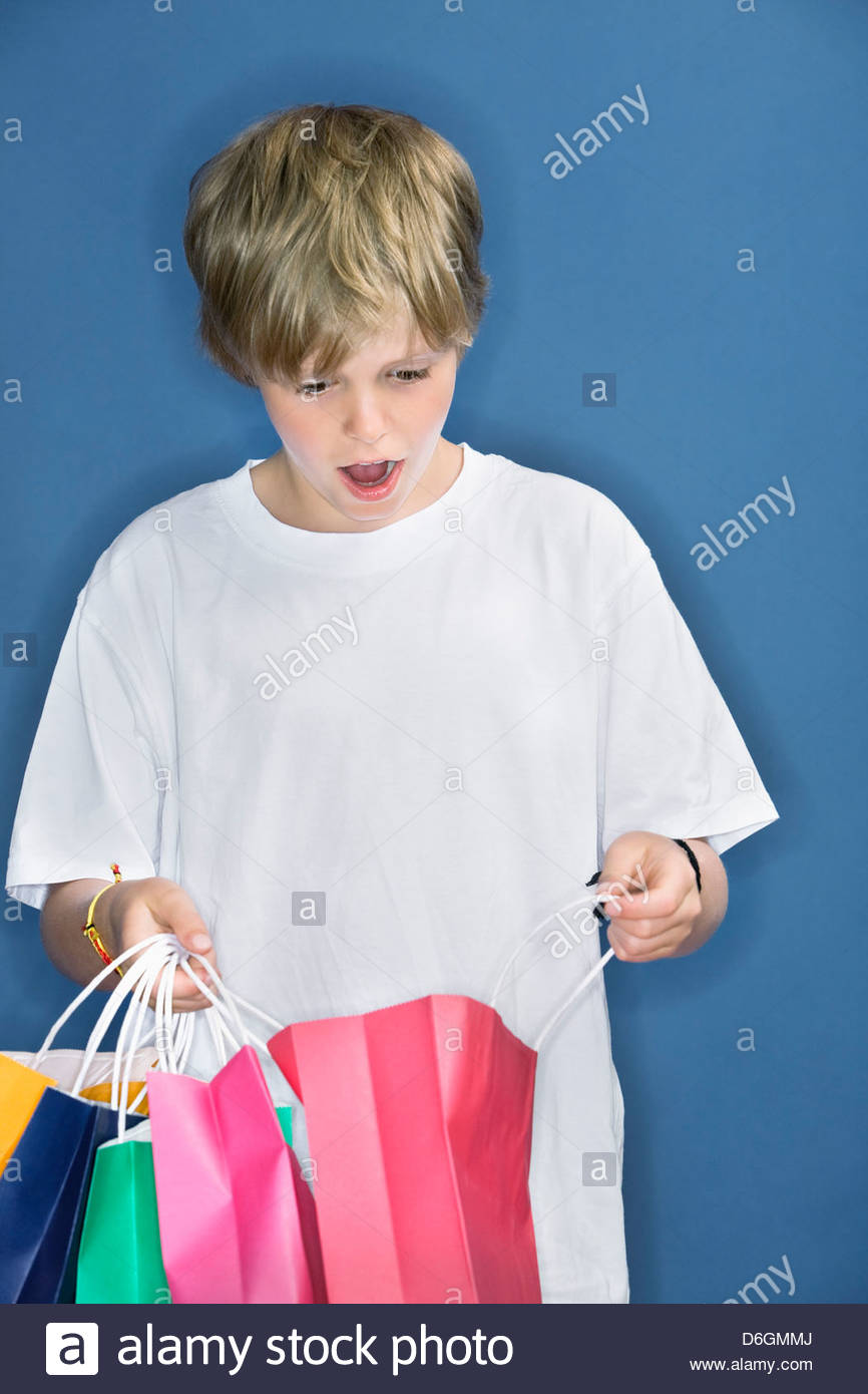 Young boy (9) holding shopping bags Munich Bavaria Germany - Stock Image