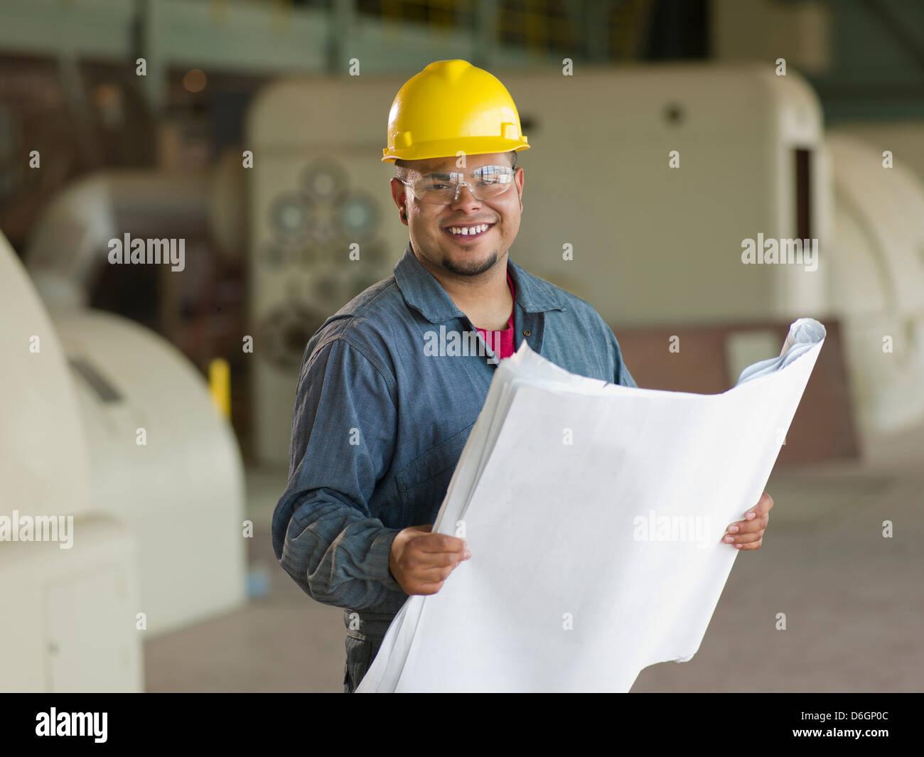Engineer reading blueprints on site - Stock Image