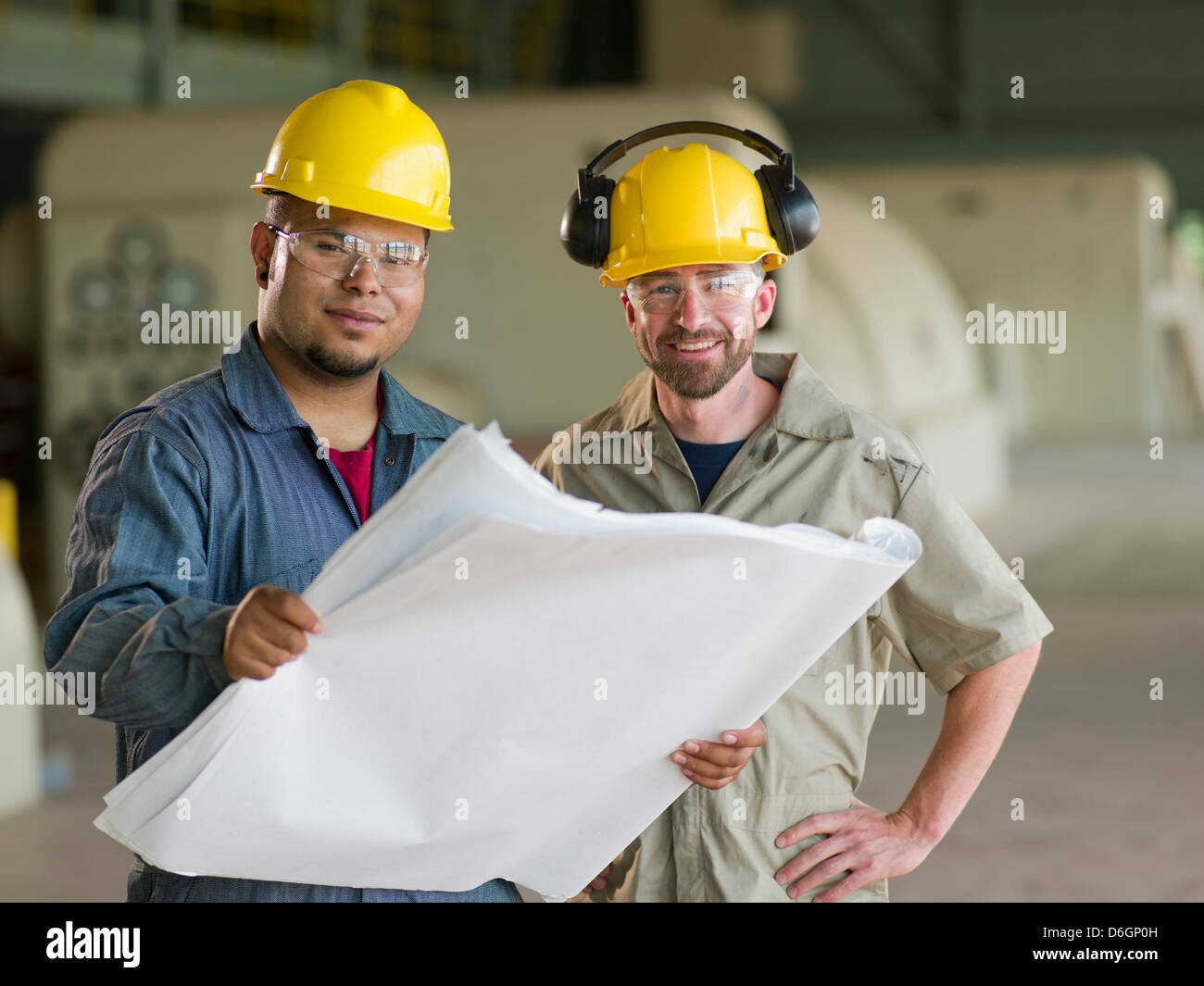Engineers reading blueprints on site - Stock Image