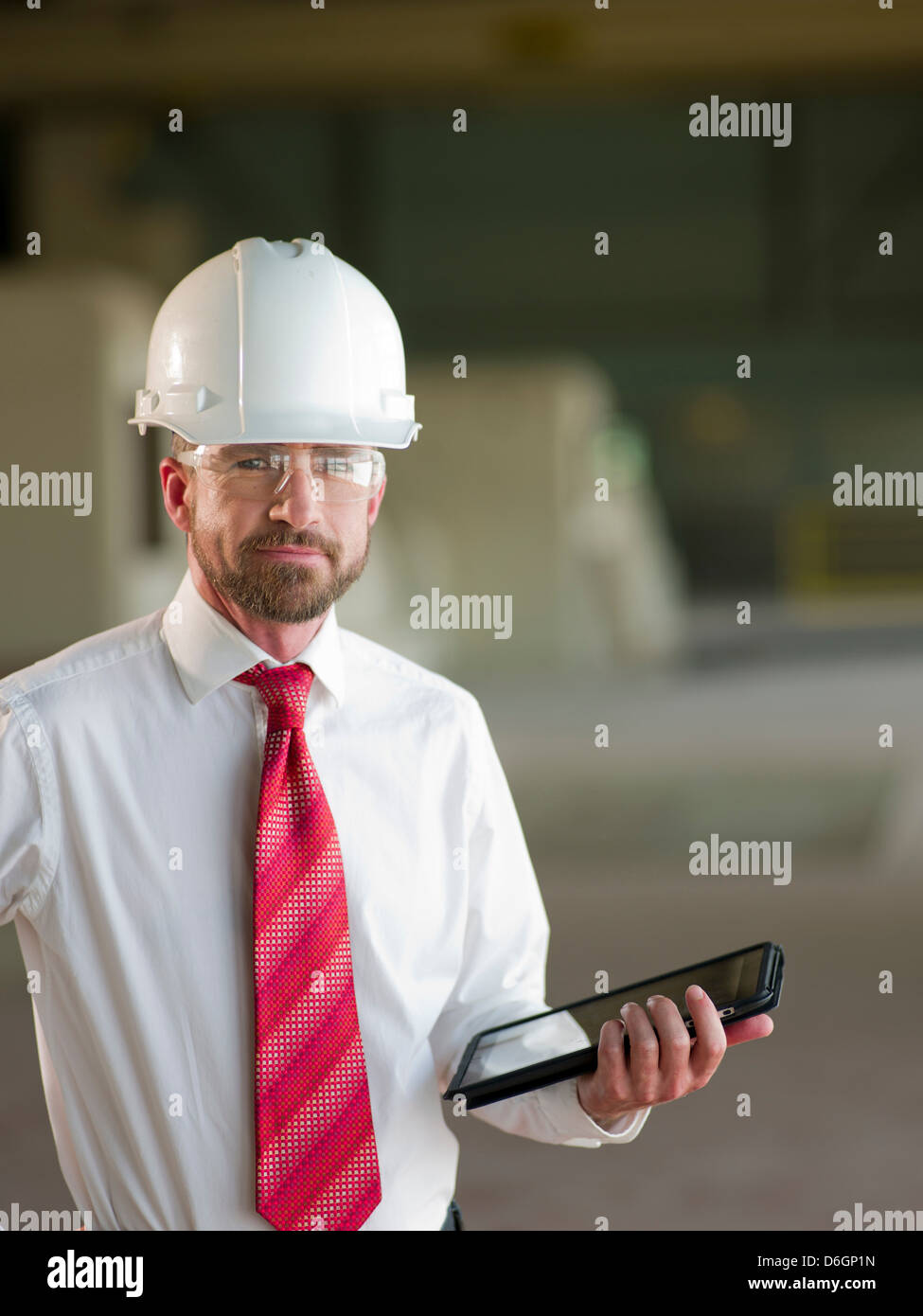 Businessman with tablet computer on site - Stock Image