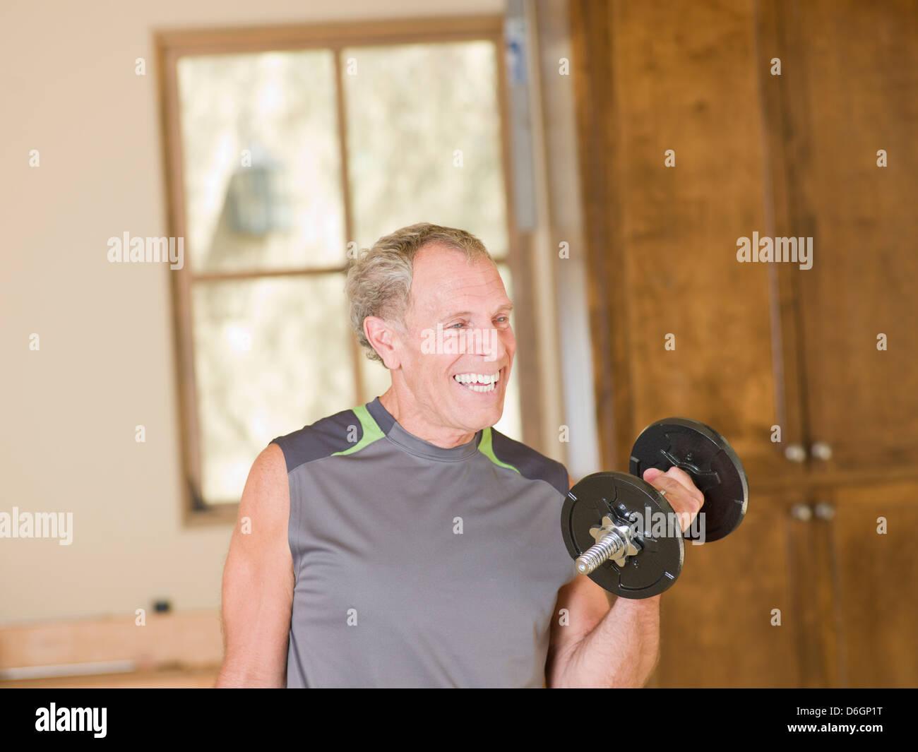 Older man lifting weights at home - Stock Image