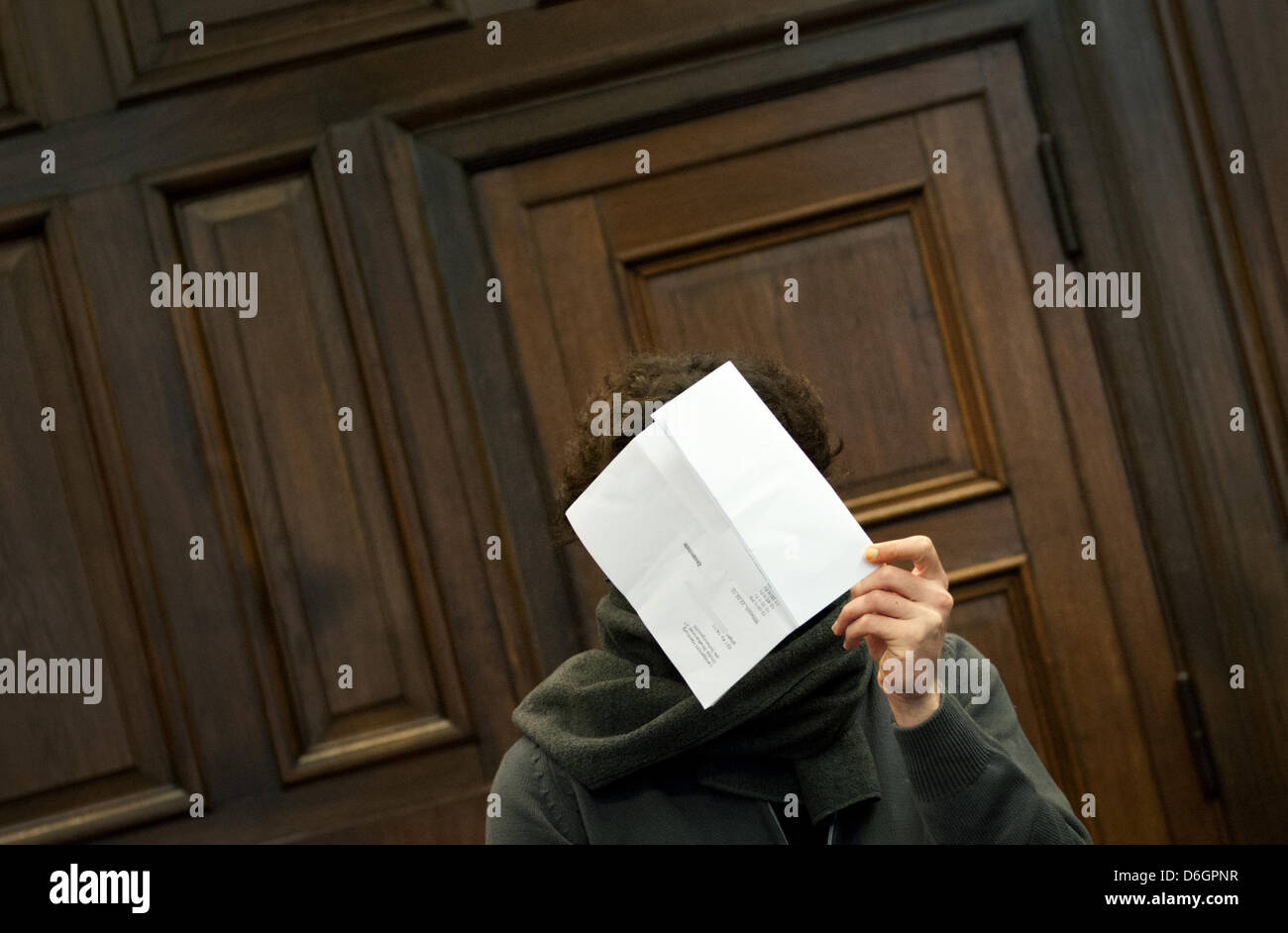 The 27 year old accused holds a piece of paper in front of his face at the District Court in Hamburg, Germany, 22 - Stock Image