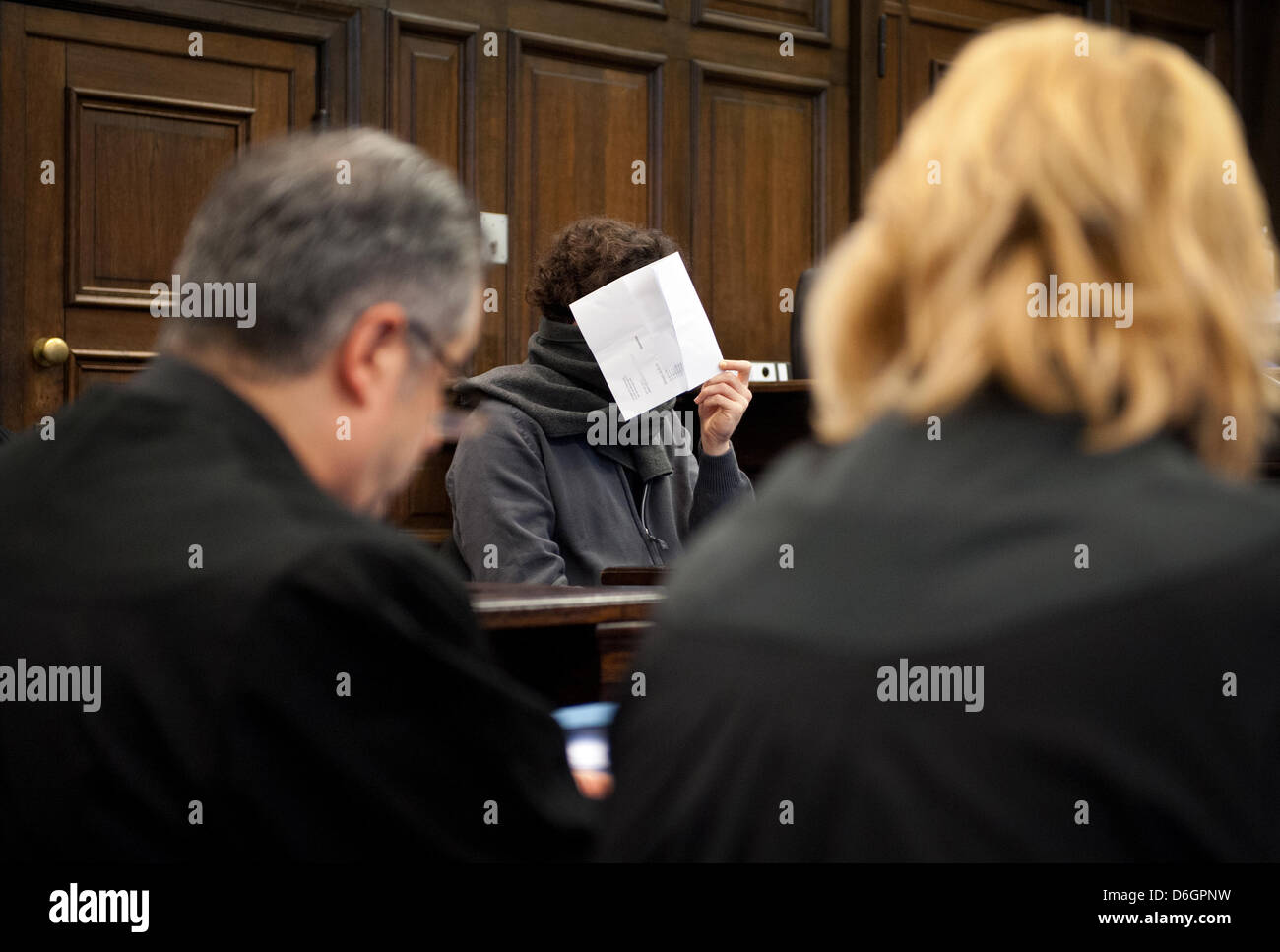 The 27 year old accused (C) holds a piece of paper in front of his face at the District Court in Hamburg, Germany, - Stock Image