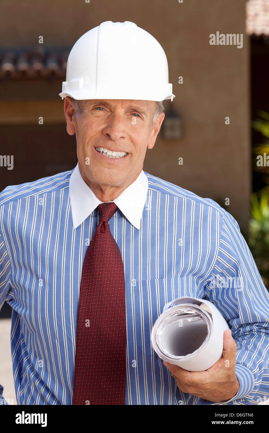 Businessman in hard hat with blueprints - Stock Image