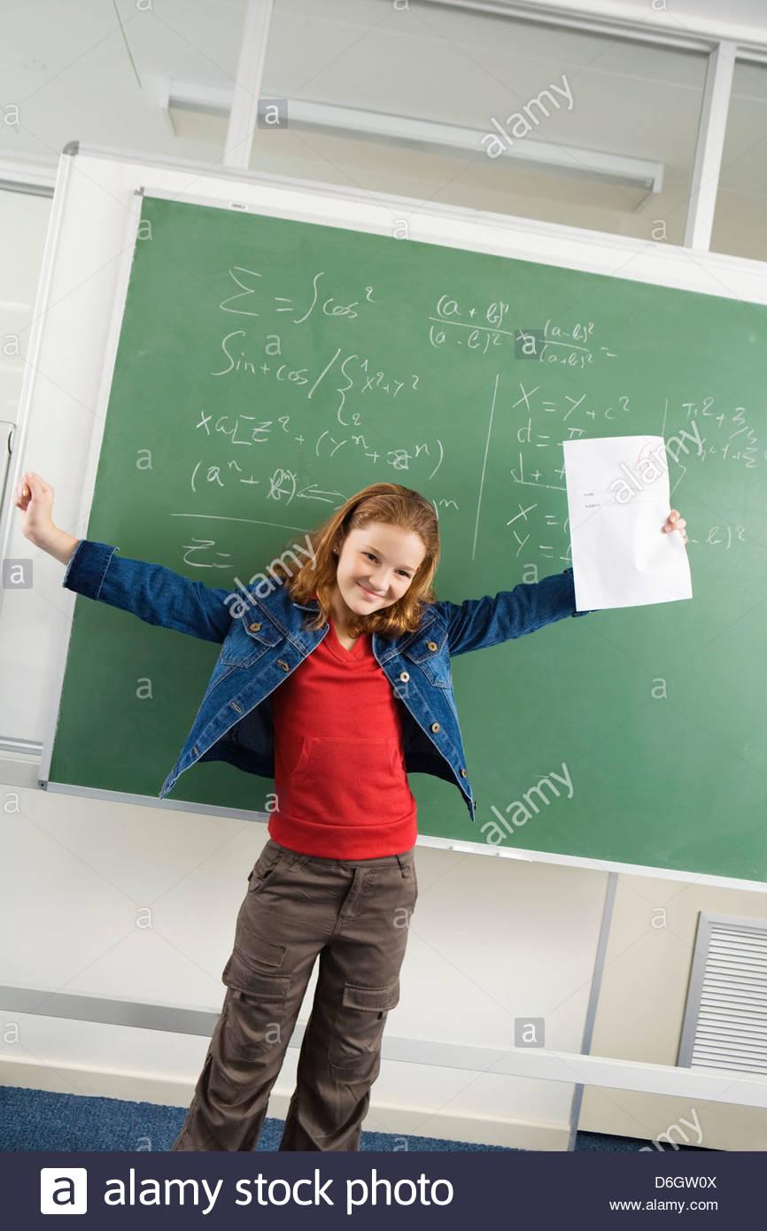School girl (10-13) writing blackboard in classroom - Stock Image