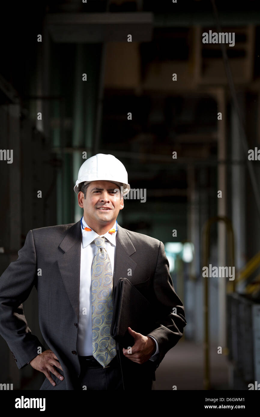 Businessman carrying folder in plant - Stock Image