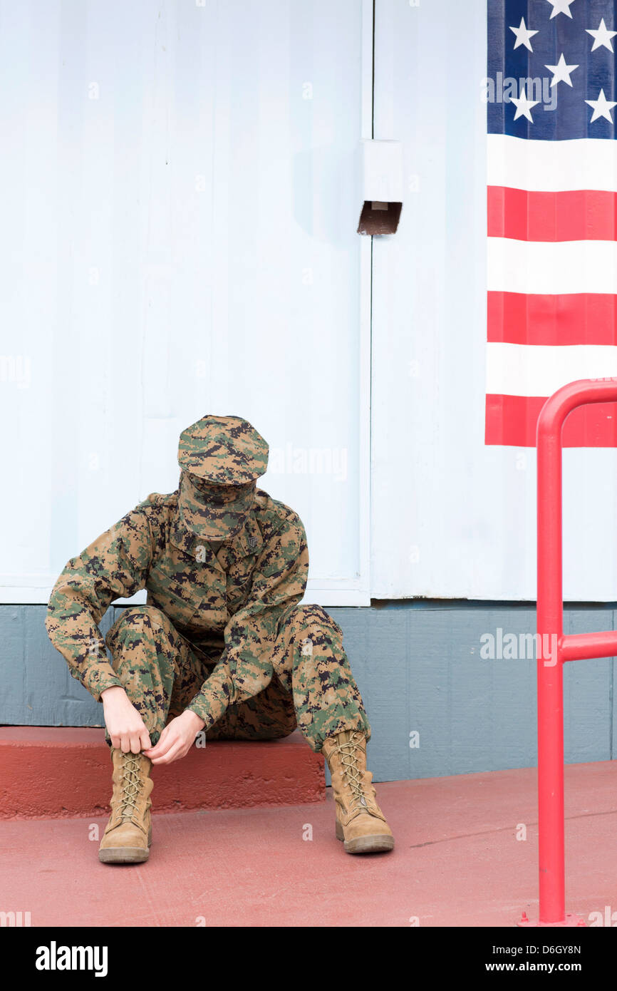 Servicewoman in camouflage by US flag - Stock Image