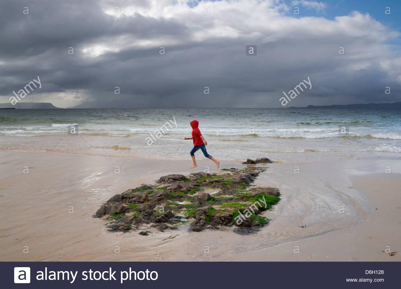 Girl running beach Morar Inverness-shire Scotland UK - Stock Image