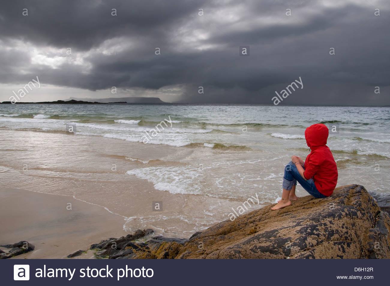 Girl sitting rock Morar Inverness-shire Scotland UK - Stock Image