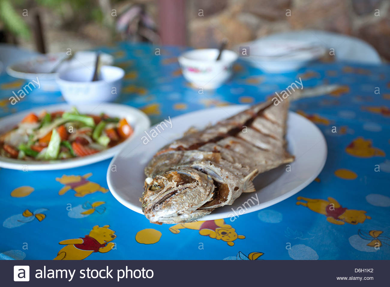 Plates of fish and vegetables on table - Stock Image