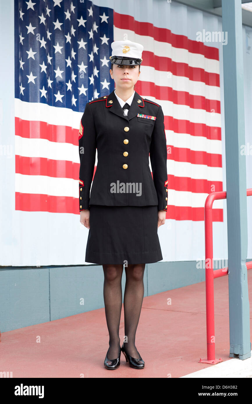 Servicewoman in dress blues by US flag - Stock Image