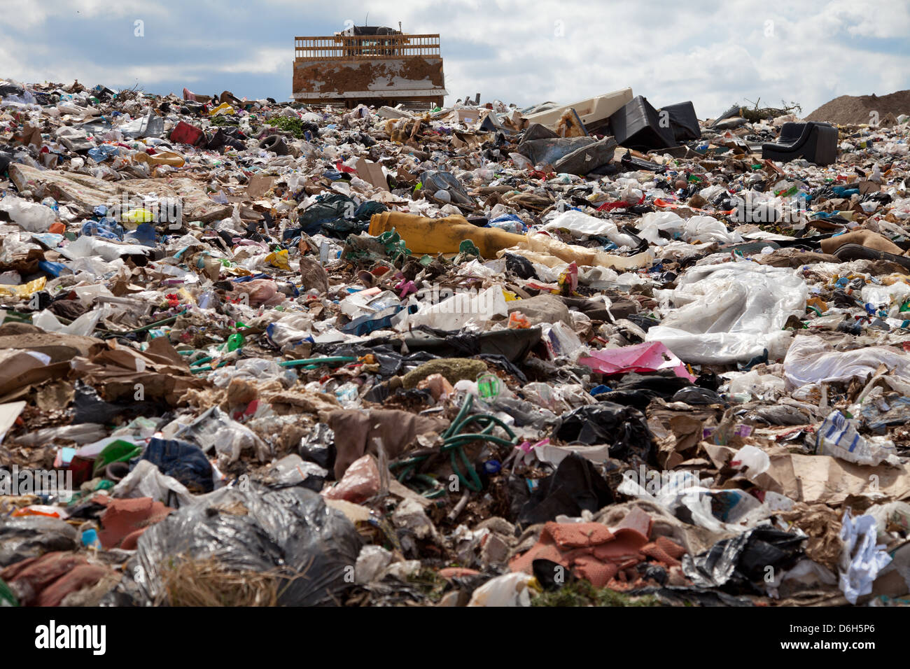 Truck managing garbage in a landfill site - Stock Image