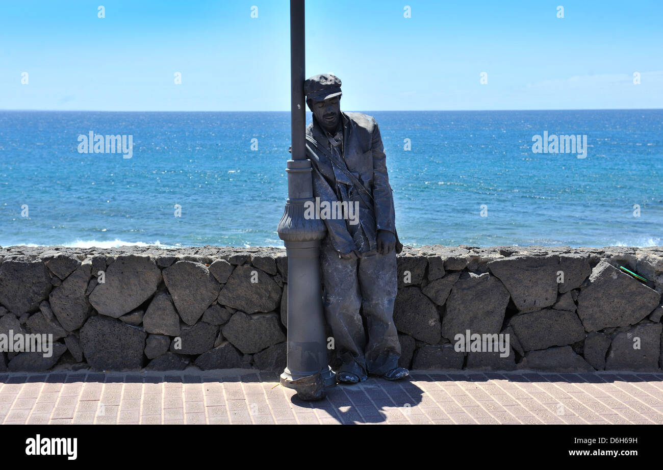 A male street performer leaning against a lamp post in Playa Blanca, Lanzarote - Stock Image