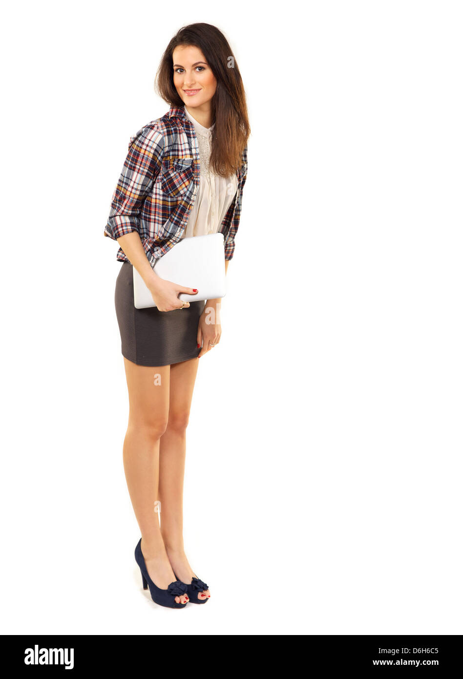 College student in the studio standing while holding her laptop - Stock Image