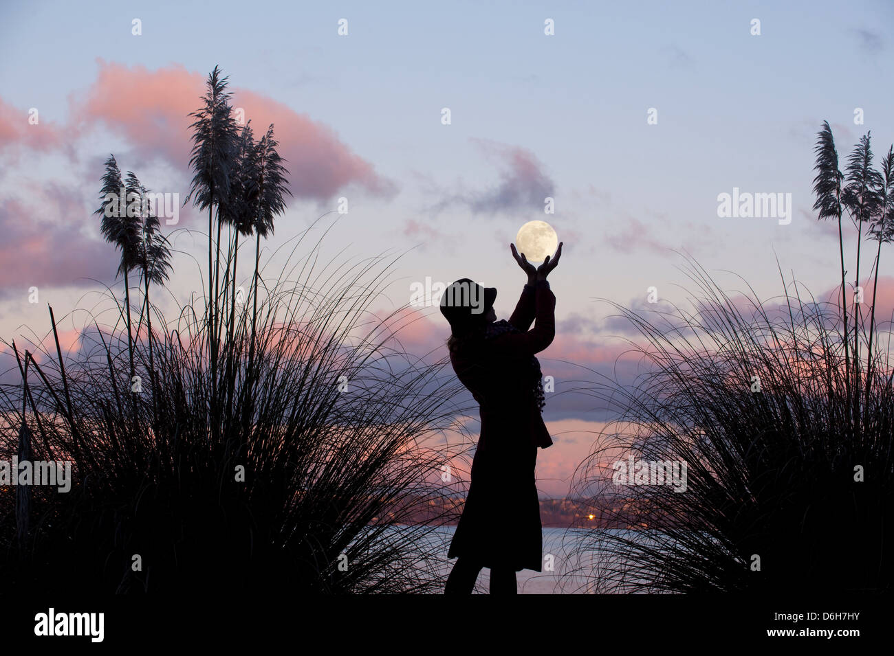 Woman cupping hands around moon Stock Photo