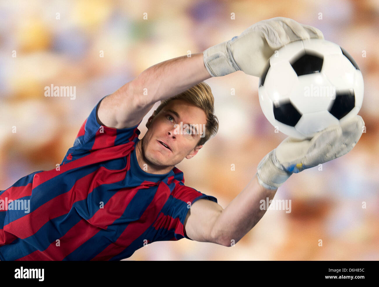 Soccer player catching ball in air - Stock Image
