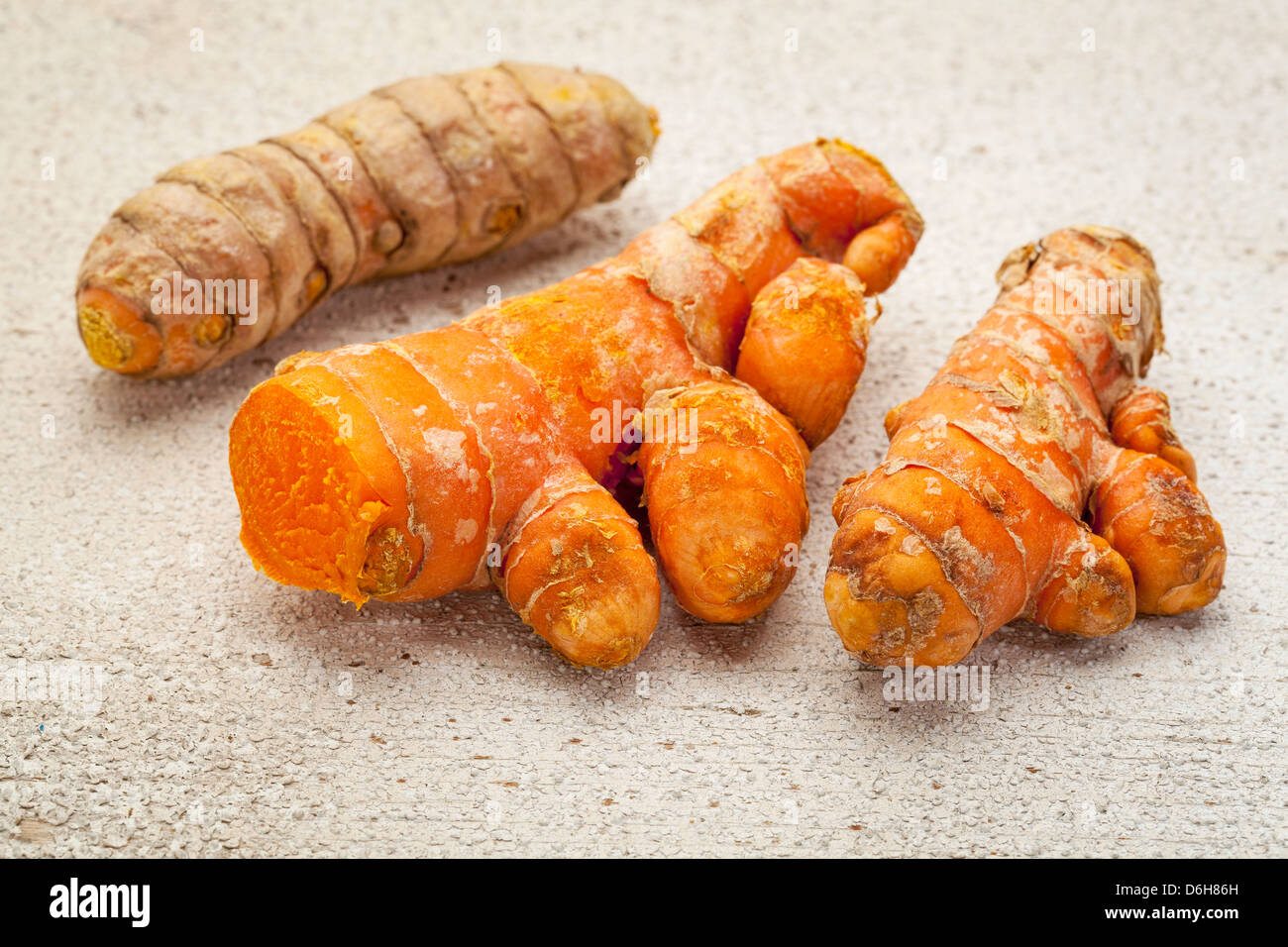 turmeric root on a white painted rough barn wood surface - Stock Image