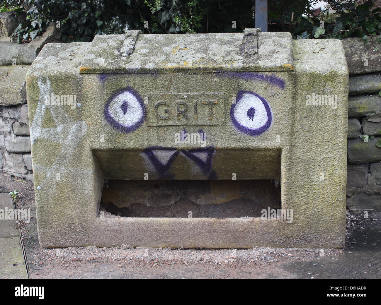 Grit bin with graffiti face painted on - Stock Image