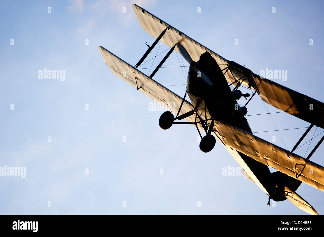 Biplane flying with blue sky in background - Stock Image