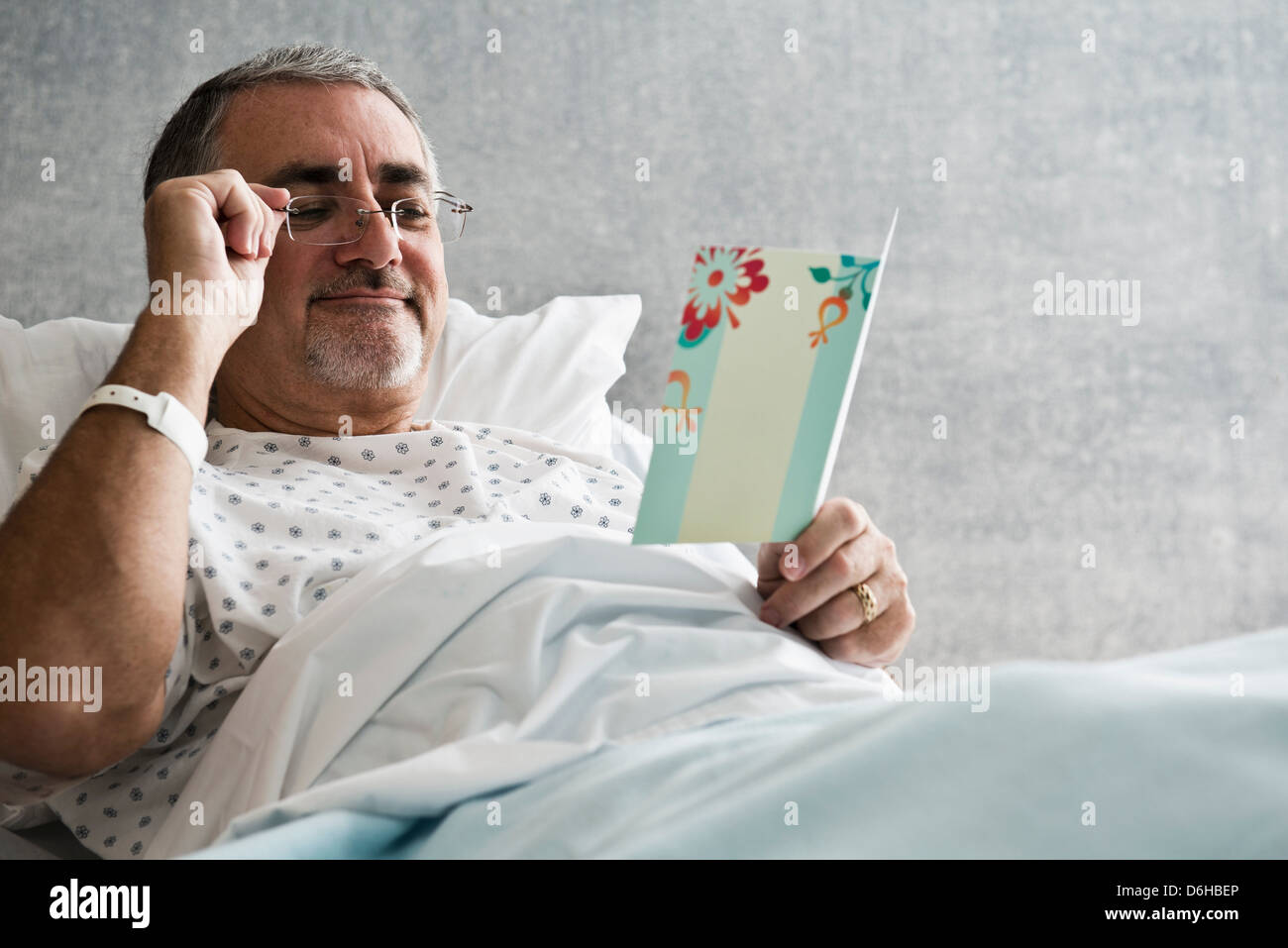 Male hospital patient looking at get well soon card - Stock Image
