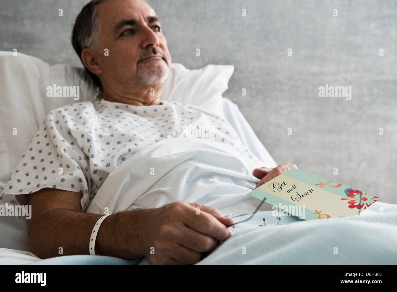 Male hospital patient with get well soon card - Stock Image