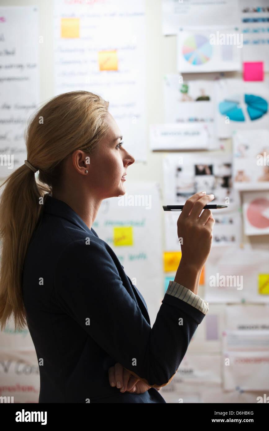 Contemplative woman holding pen - Stock Image