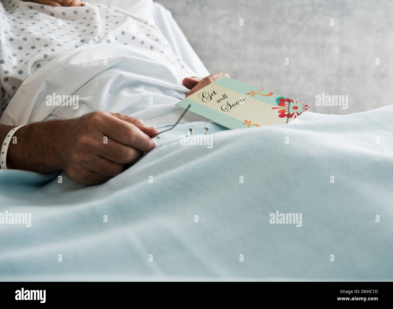 Hospital patient with get well soon card - Stock Image