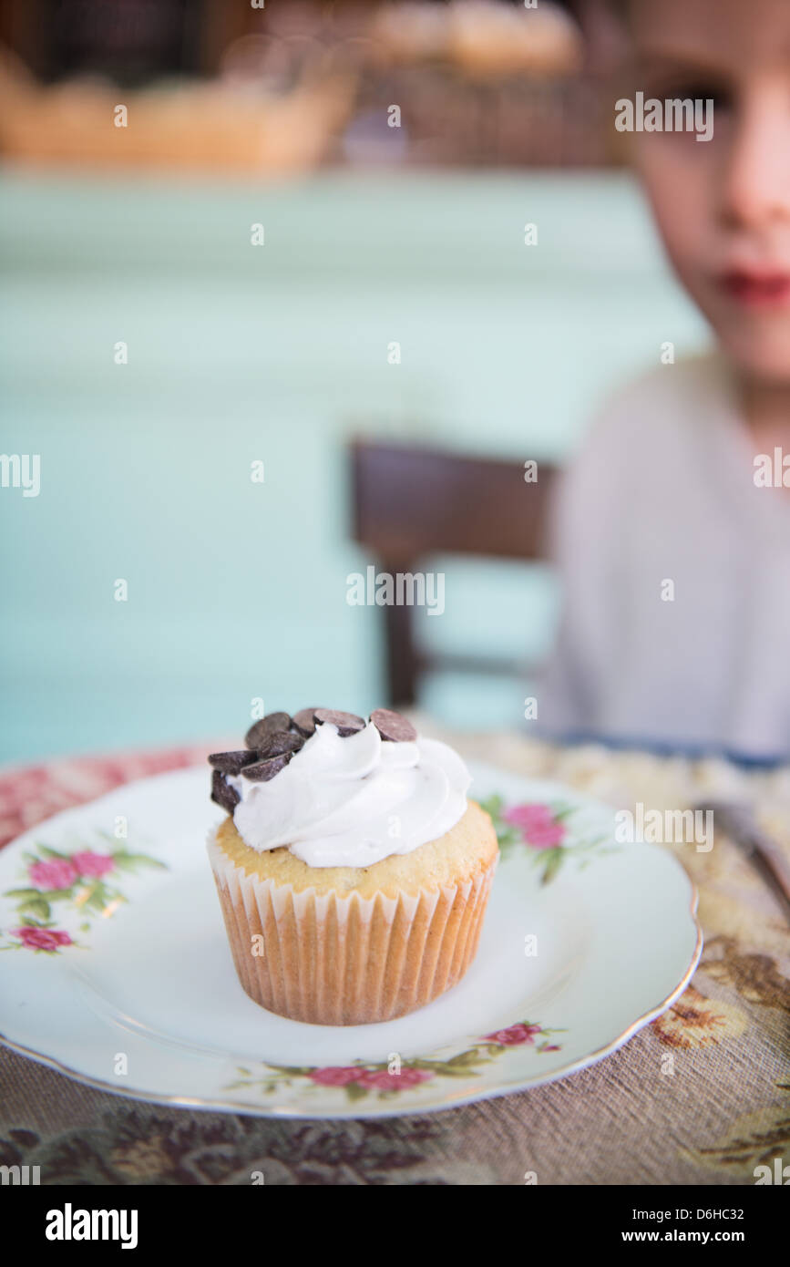 Boy Looking And Eating A Cupcake At Fuschia Epicerie Fleur Store In