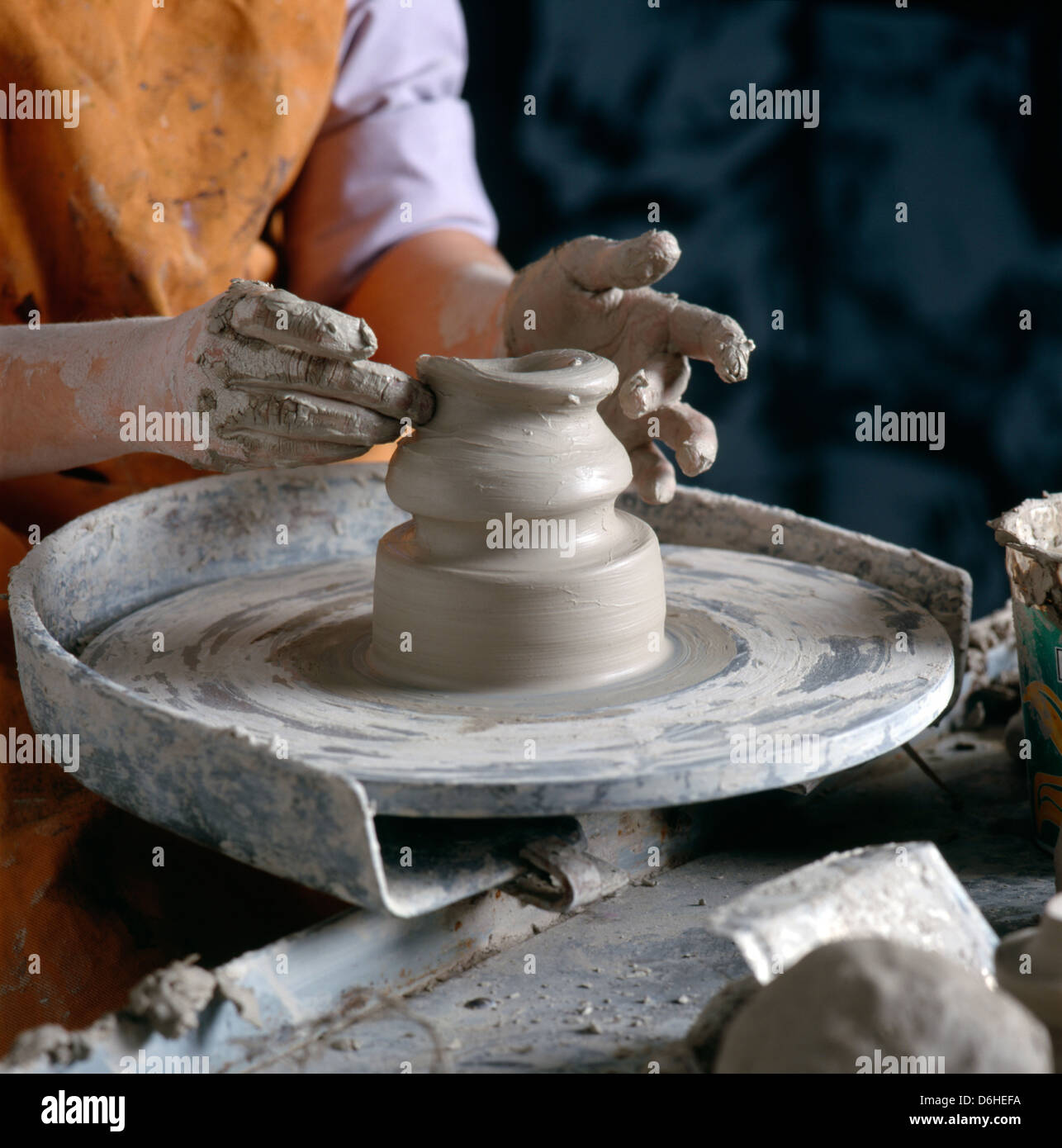Close up of teenage girl's hands shaping pottery on a pottery wheel in a high school art class. - Stock Image