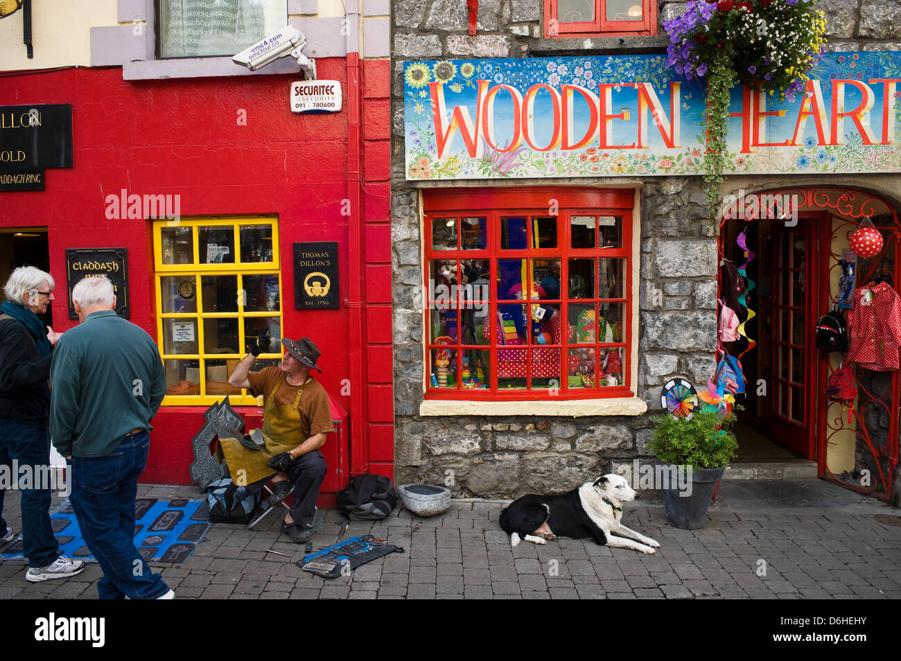 Artist chats to passers bye High Street Galway City Ireland. - Stock Image