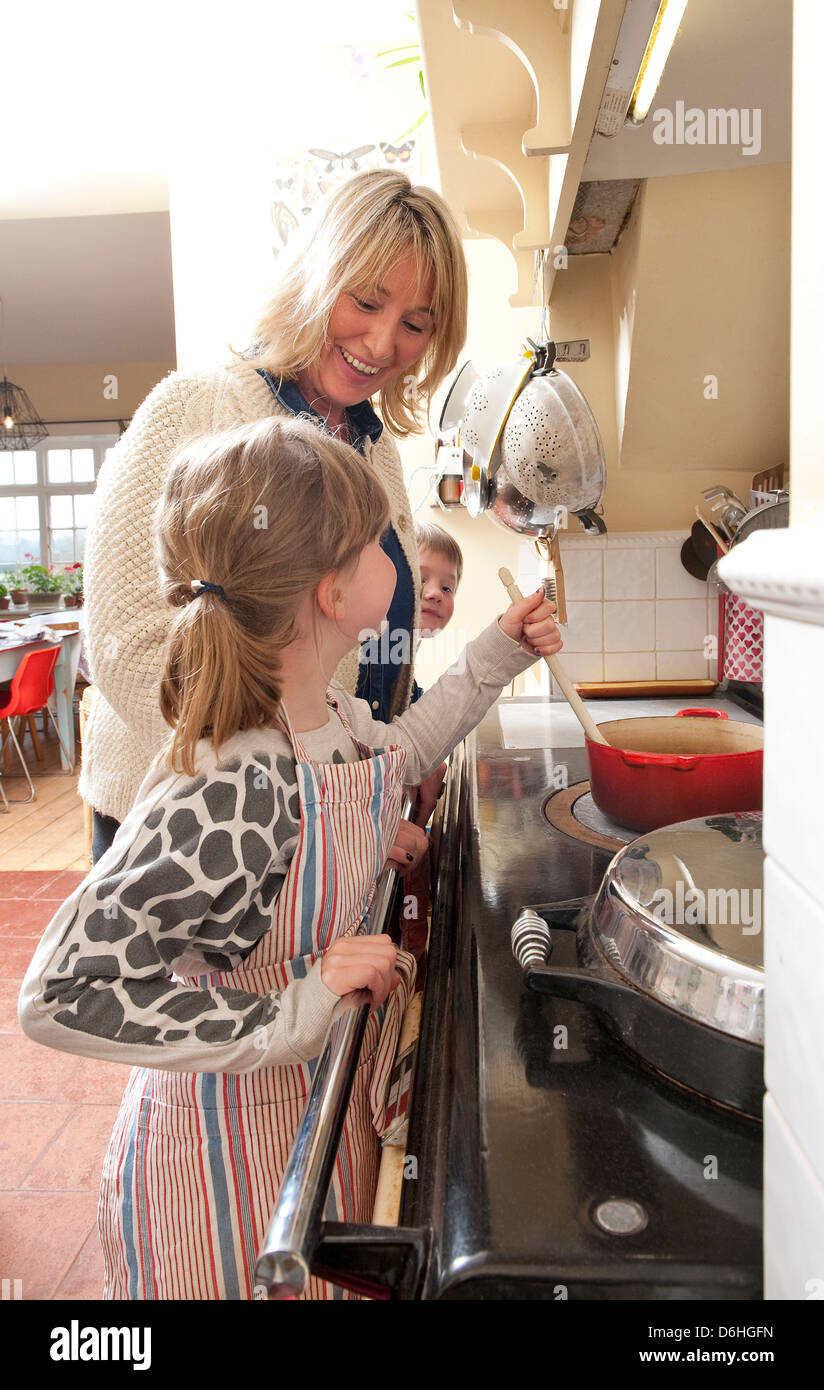 mother and daughter cooking on aga stove - Stock Image