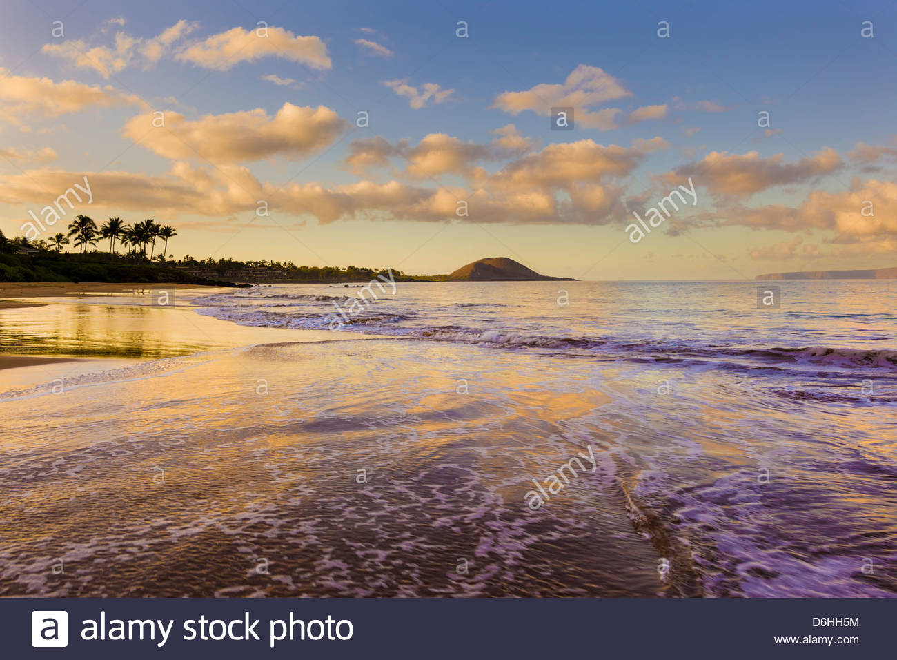 Sunrise and incoming gentle waves on Po'olenalena Beach in Makena on the island of Maui in the State of Hawaii - Stock Image