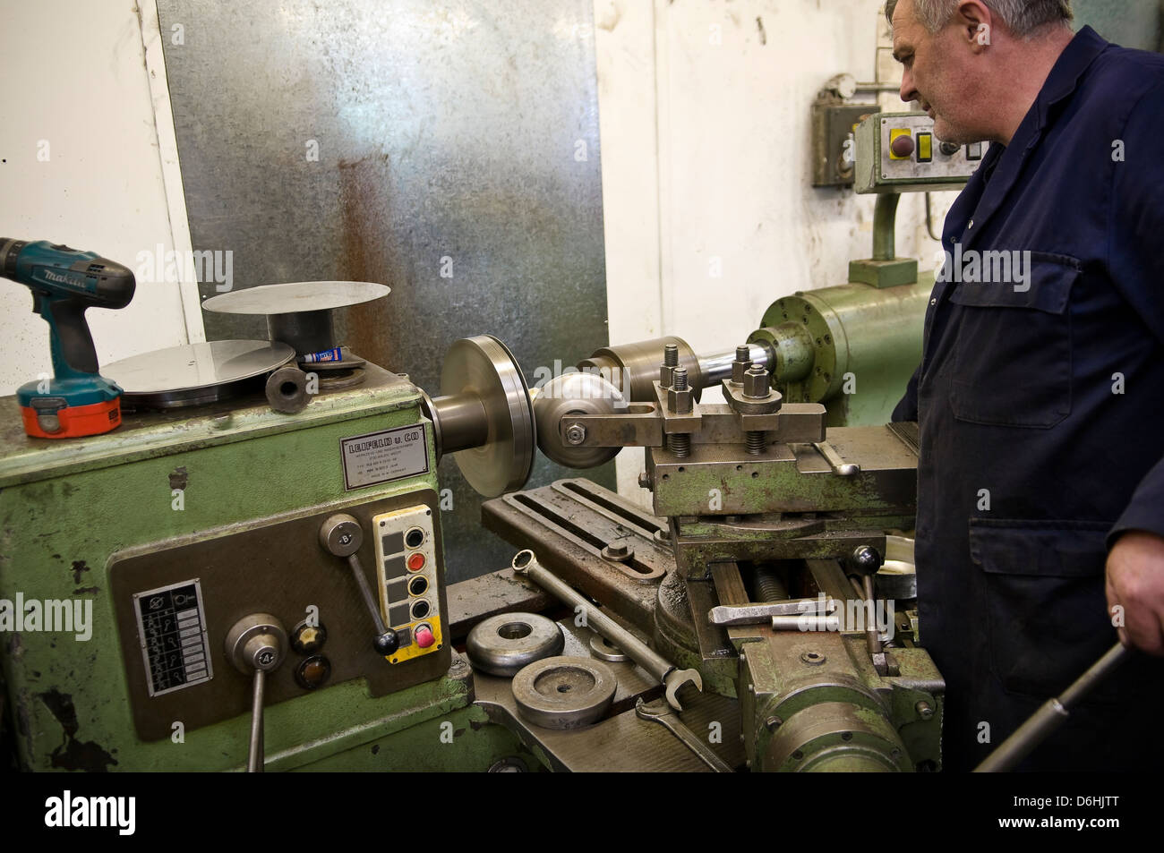 Flat steel plate being spun to create 3 dimensional object on an industrial metal spinning lathe. - Stock Image
