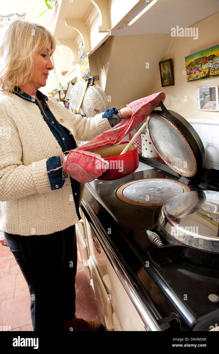 woman cooking on aga stove - Stock Image