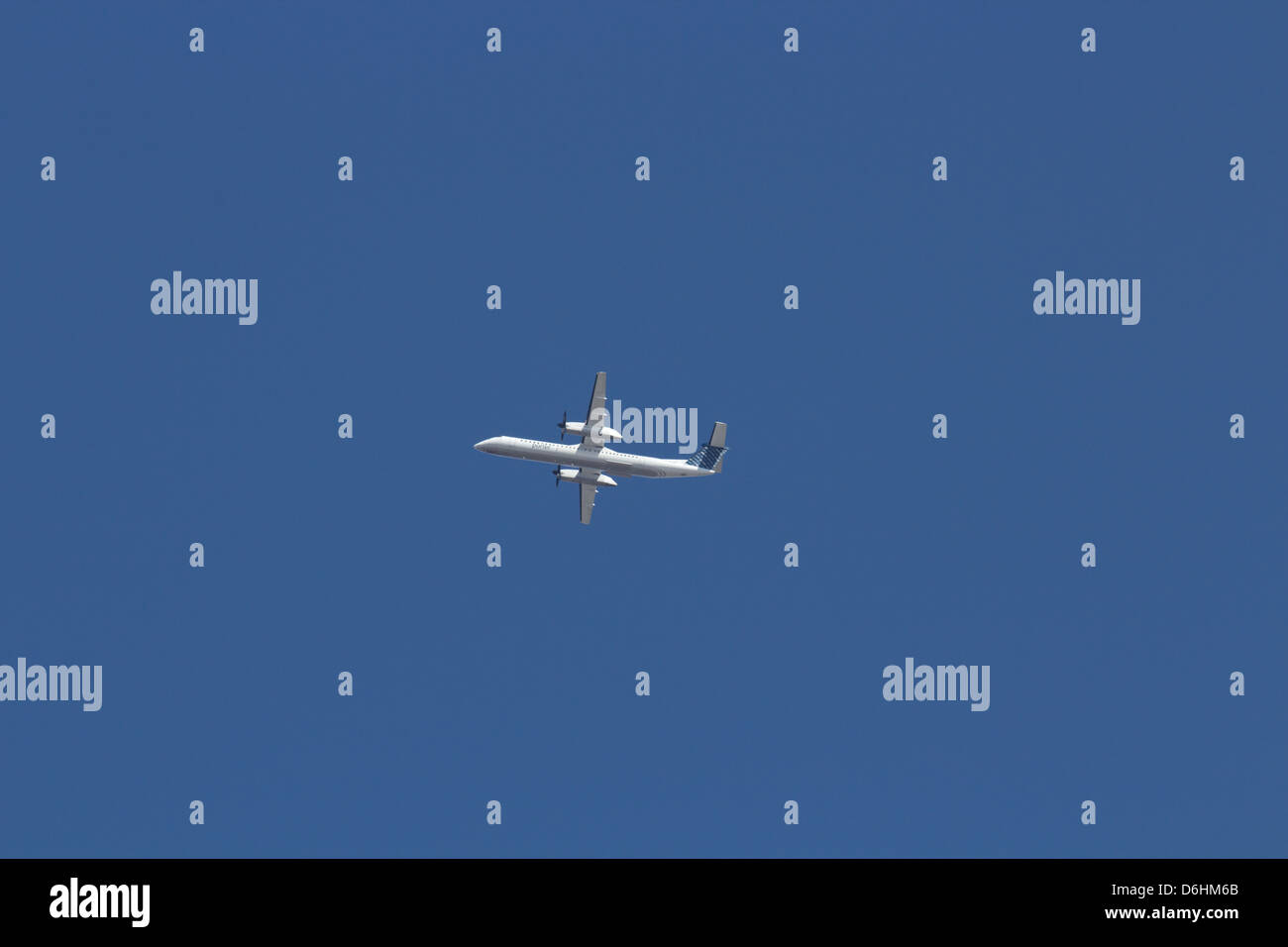 Dash 8 400 flying in a bright blue sky - Stock Image