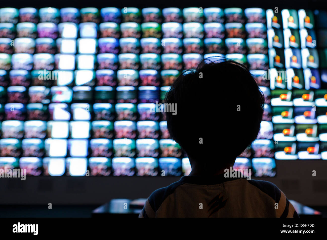 Small boy watching a large video screen - Stock Image