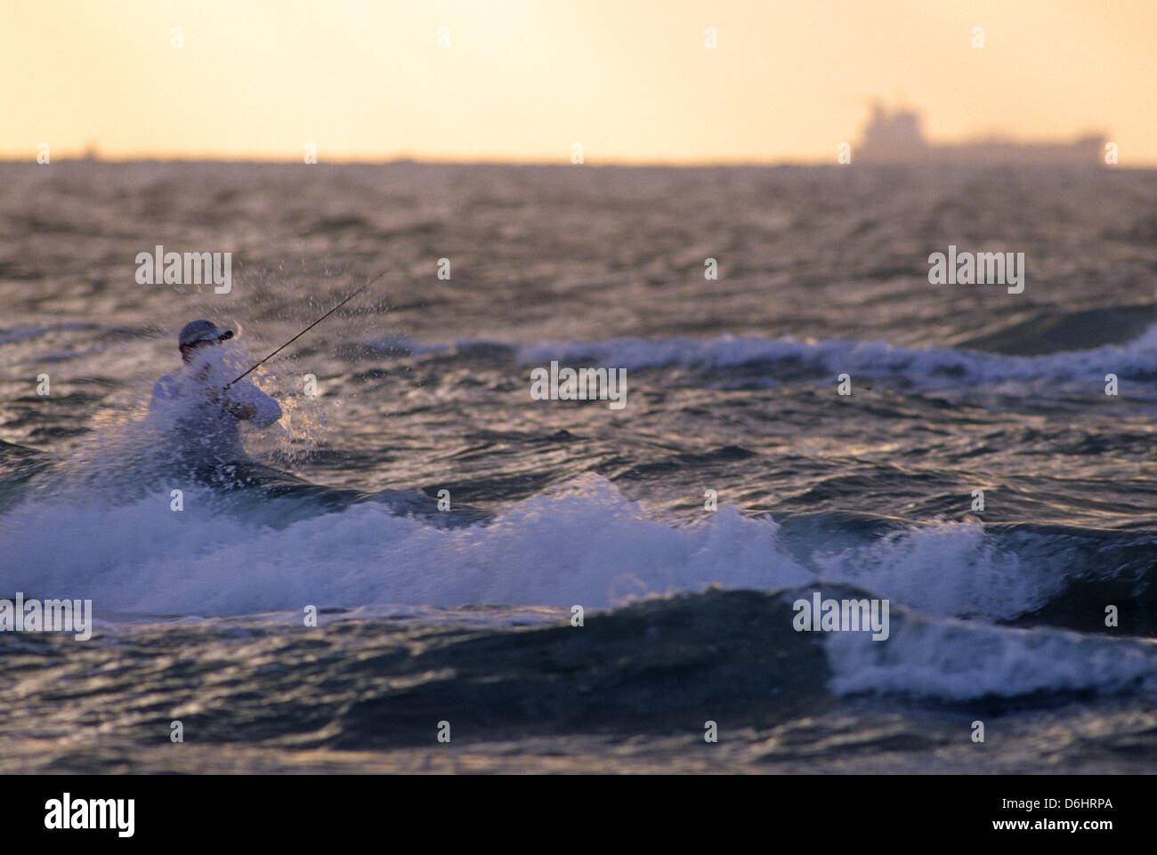 Surf fisherman casting in the waves at sunrise on Mustang Island Texas - Stock Image