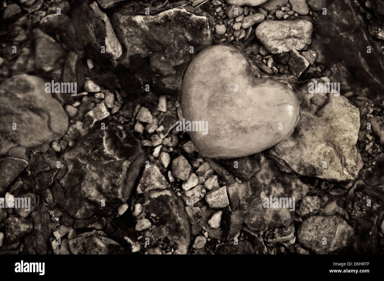 Black and White Stone Heart Amid Pebbles in a Stream - Stock Image