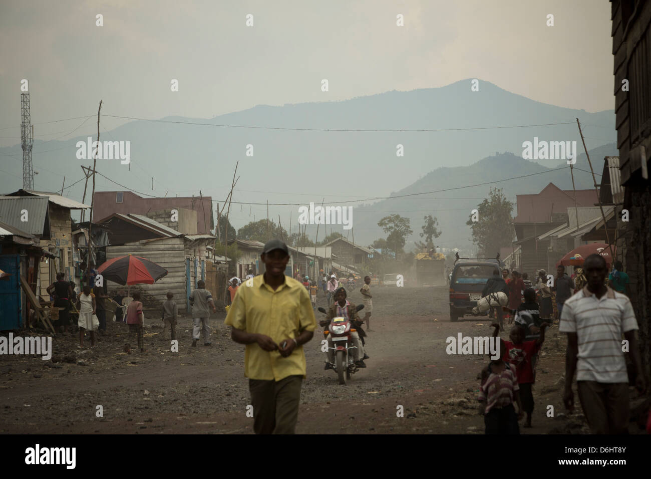 Car and pedestrian traffic move through the dusty streets of Goma, DRC. - Stock Image