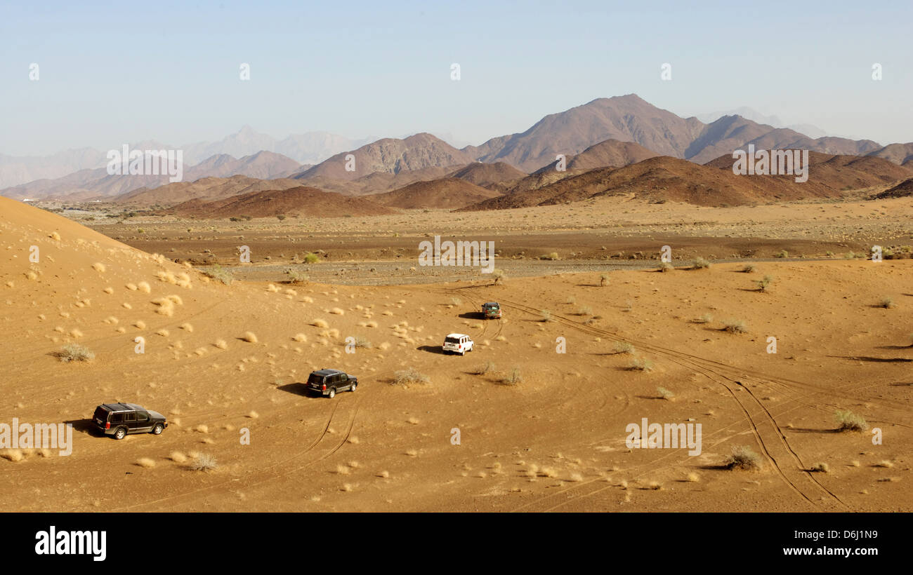 A convoy of 4x4 vehicles driving offroad in Oman. - Stock Image