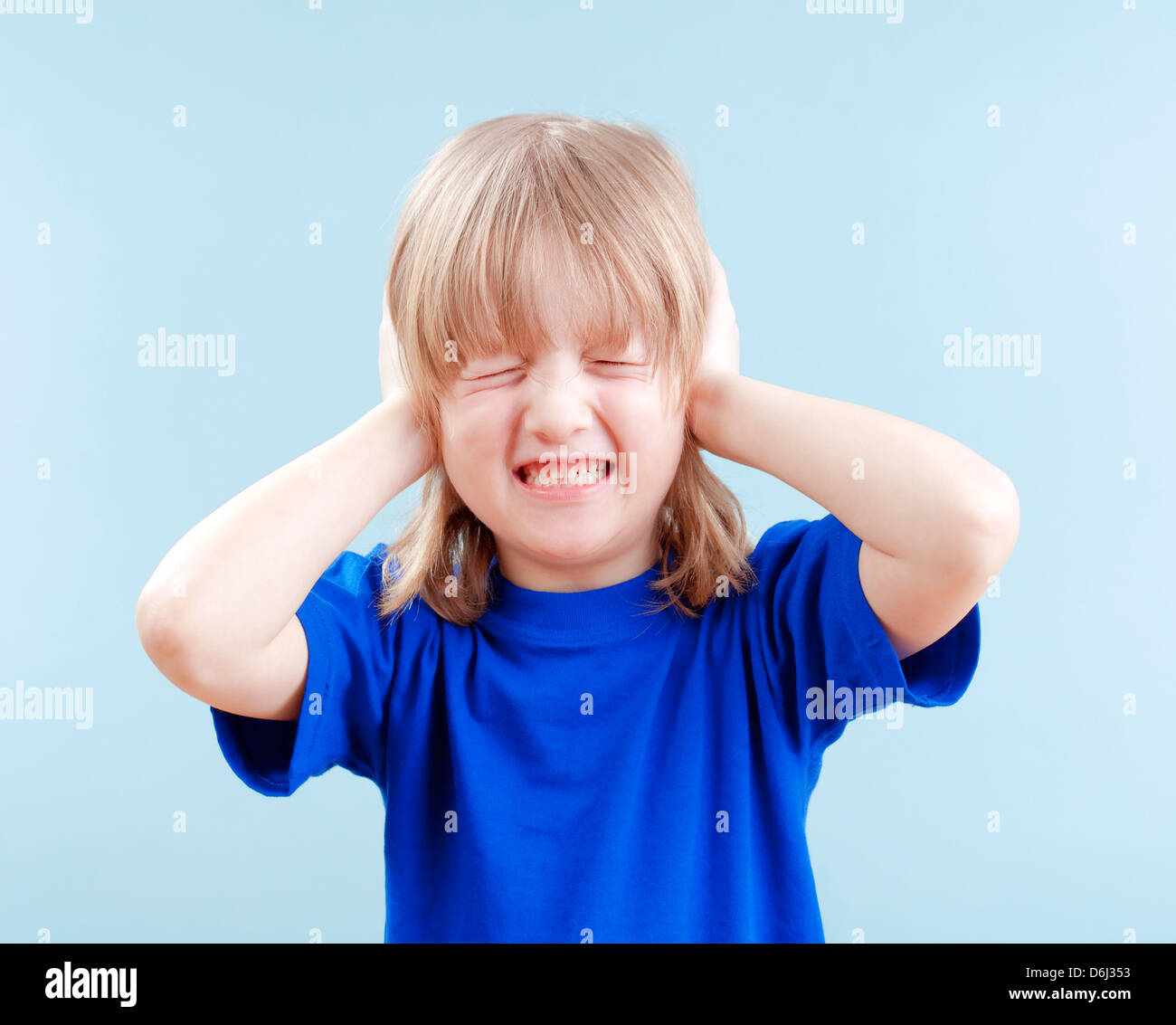 upset boy with long blond hair covering his ears as protection - isolated on blue - Stock Image