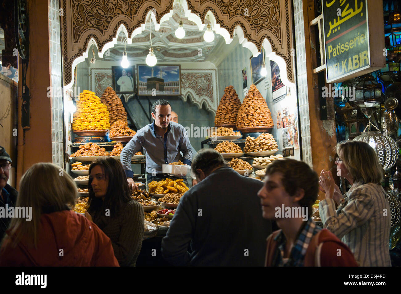 Shop keeper selling sweet cakes to tourists in the souks at night, Marrakech (Marrakesh, Morocco, North Africa, - Stock Image